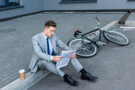 Businessman reading newspaper near coffee to go and bike on walkway