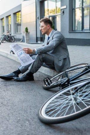 Photo pour Jeune homme d'affaires lisant un journal assis sur une passerelle près du vélo au premier plan flou - image libre de droit