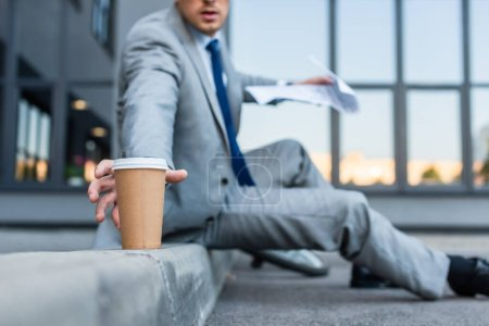 Photo for Cropped view of businessman taking takeaway coffee while holding newspaper on blurred background on walkway - Royalty Free Image