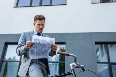 Concentrated businessman reading newspaper near bike outdoor