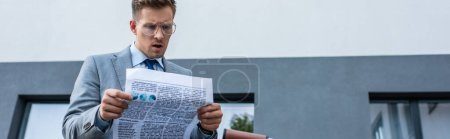Concentrated businessman reading newspaper near building, banner