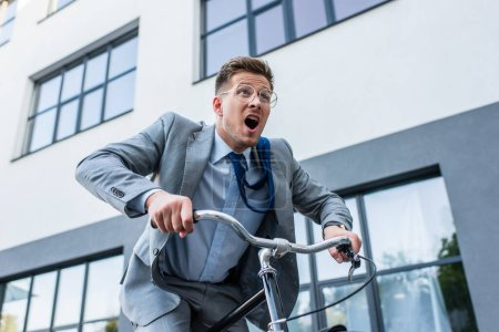 Excited businessman cycling near building outdoors