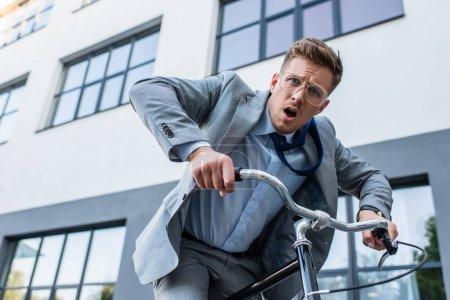 Photo pour Homme d'affaires confus regardant la caméra tout en faisant du vélo près du bâtiment - image libre de droit