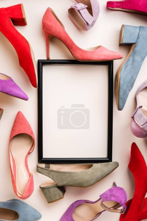 Photo pour Top view of heeled shoes and empty frame on white background - image libre de droit