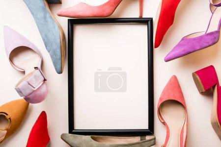 vista superior de zapatos de tacón y marco vacío sobre fondo blanco