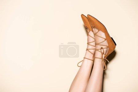 Photo pour Vue recadrée des jambes féminines en daim marron chaussures plates sur fond beige - image libre de droit
