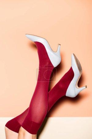Photo pour Vue recadrée des jambes féminines en chaussettes rouges et chaussures bleues sur fond de pêche - image libre de droit