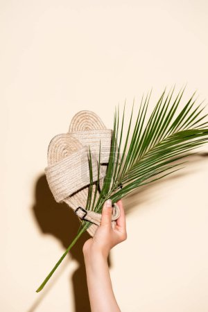 cropped view of woman holding summer braided sandals and palm leaf on beige background