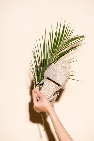 Photo pour Vue recadrée d'une femme tenant des sandales tressées d'été et une feuille de palmier sur fond beige - image libre de droit
