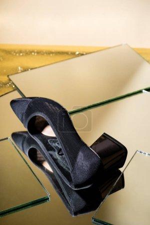 Photo pour Élégante chaussure à talons noirs sur surface miroir - image libre de droit