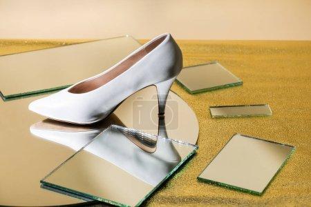 elegant white heeled shoe on mirror surface
