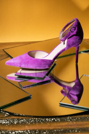 elegant violet suede heeled shoe on mirror surface on yellow background