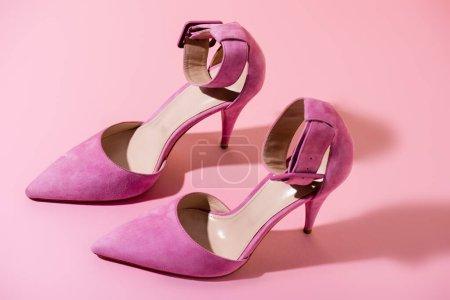 Photo pour Paire d'élégantes chaussures à talons en daim sur fond rose - image libre de droit