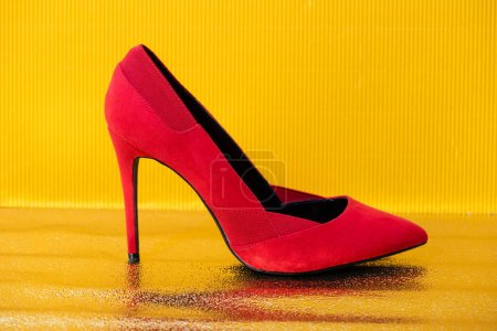 Photo for Elegant red suede heeled shoe on yellow background - Royalty Free Image