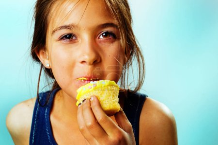 Young girl biting cupcake closeup.