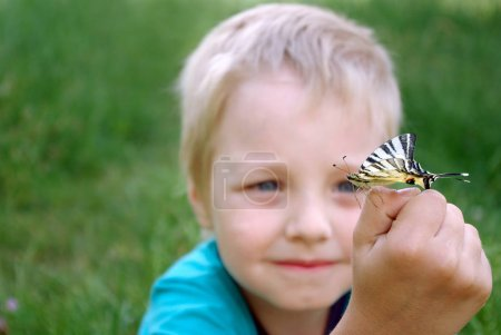 Photo for Butterfly sitting on the hand of a child. Child with a butterfly. Butterfly on the hand of a little boy. Selective focus. - Royalty Free Image