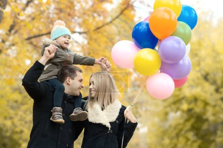 happy family with little child and air-balloons, outing in autumn park