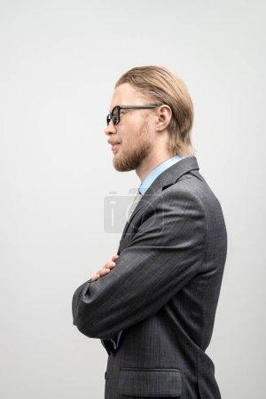 Photo pour Portrait vertical un homme homme d'affaires ou un employé de bureau dans des lunettes, vue de côté, sur fond gris - image libre de droit