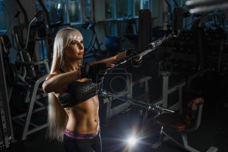 Photo pour Femme blonde musclée faisant tirer les bras d'entraînement avec des sangles de fitness trx dans la salle de gym. Concept entraînement mode de vie sain sport. Fille dans la salle de gym exercices main tirant le bloc . - image libre de droit