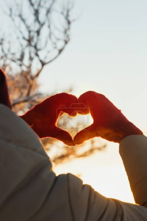 Photo for Heart shape symbol of the women mittens in winter frosty sunset. Concept of winter, dating, valentines day and love. - Royalty Free Image