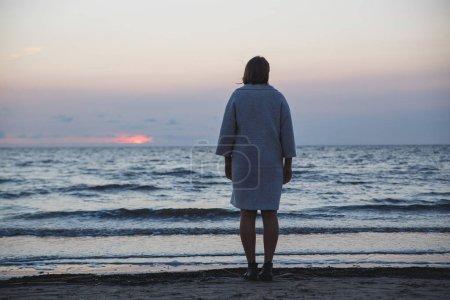 Photo pour Femme debout seul sur la plage, sous le ciel nuageux par derrière. - image libre de droit