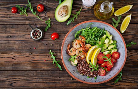 Photo for Delicious healthy Buddha bowl with shrimps, tomato, avocado, quinoa, lemon and arugula on the wooden table. Healthy food. Top view - Royalty Free Image