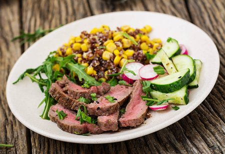 Healthy dinner. Bowl lunch with grilled beef steak and quinoa, corn, cucumber, radishes and arugula on wooden background. Meat salad.