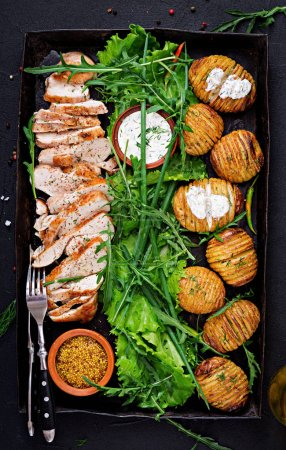 Chicken fillet cooked on a grill with a garnish of baked potatoes. Dietary meal. Healthy food. Top view. Flat lay