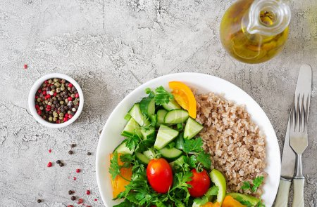 Photo for Diet menu. Healthy vegetarian salad of fresh vegetables - tomatoes, cucumber, sweet peppers and porridge on bowl. Vegan food. Flat lay. Top view with copy space - Royalty Free Image