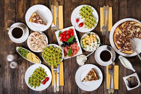 Photo for Breakfast food table. Festive brunch set, meal variety with spinach waffles, salmon, cheese, olives, chicken rolls and cheesecake. Top view. Flat lay - Royalty Free Image