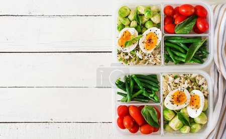 Photo for Vegetarian meal prep containers with eggs, brussel sprouts, green beans and tomatoes on white wooden background - Royalty Free Image