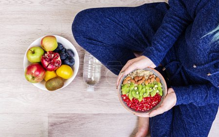 Photo for Fitness and healthy lifestyle concept. Female is resting and eating a healthy oatmeal after a workout. Top view. - Royalty Free Image