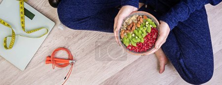 Photo for Fitness and healthy lifestyle concept. Female is resting and eating a healthy oatmeal after a workout. Banner. Top view. - Royalty Free Image