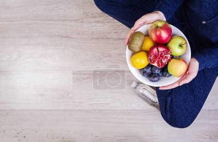 Photo for Girl holding white plate with apples, plums, kiwi and pomegranate. Healthy eating. Fitness and healthy lifestyle concept. Top view - Royalty Free Image