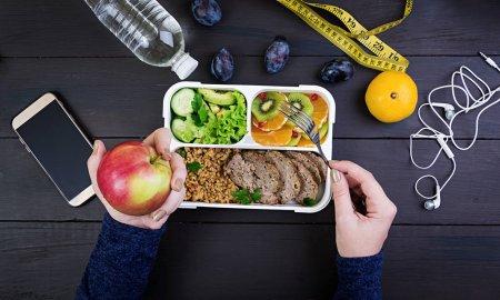 Vista superior que muestra las manos comiendo un almuerzo saludable con bulgur, carne y verduras frescas y frutas en una mesa de madera. Concepto de fitness y estilo de vida saludable. Una lonchera. Vista superior