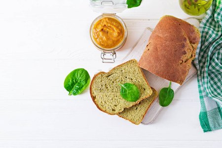 Photo for Freshly baked spinach bread on a white wooden table - Royalty Free Image