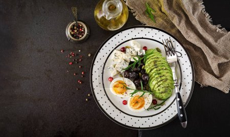 Photo for Top view of plate of blue cheese, avocado, boiled egg, olives on a black background - Royalty Free Image