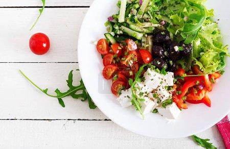 Photo pour Alimentation saine. Salade grecque de concombre frais, tomate, poivron, laitue, oignons, fromage feta et olives noires, huile d'olive. Bol de Bouddha. Vue de dessus - image libre de droit