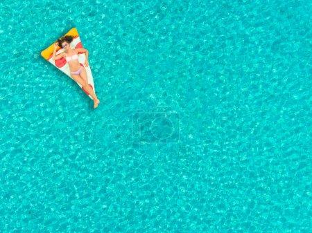 Photo pour Vue aérienne de femme flottant sur matelas gonflable pizza, relaxantes et souriant. - image libre de droit