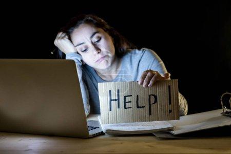 Photo pour Jeune étudiant fatigué et stressé travaillant tard dans la nuit sur ordinateur portable tenant signe HELP . - image libre de droit