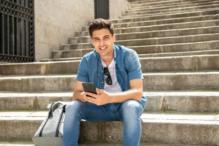 Young happy male student in jeans denim clothes sitting on stairs at street of modern European city and texting on modern smartphone