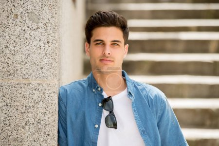 Photo for Outdoor portrait of modern trendy handsome Hispanic young man in city. Urban background - Royalty Free Image