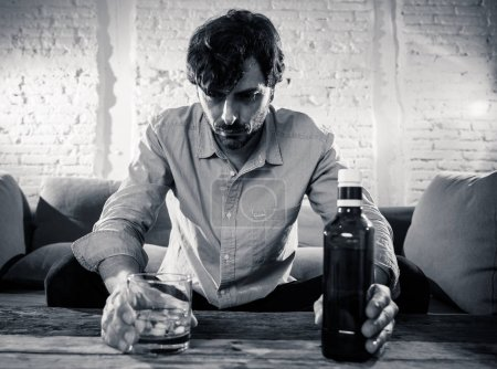 Photo for Drunk alcoholic lain business man drinking whiskey from the bottle and glass depressed wasted and sad at home couch in alcohol abuse and alcoholism concept - Royalty Free Image