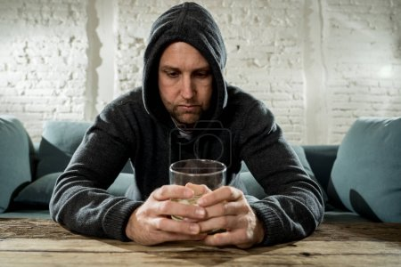 drunk alcoholic unemployed man drinking whiskey from the glass and bottle depressed wasted and sad at home couch in alcohol abuse and alcoholism concept