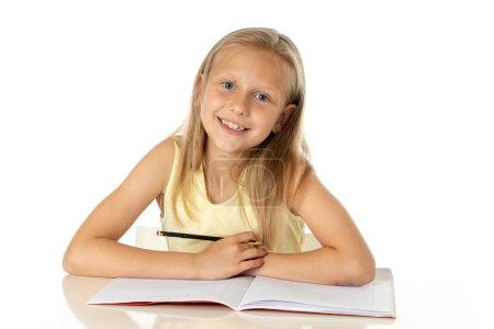 Photo pour Éducation à domicile concept. mignonne jeune fille caucasienne blonde étudiant ou faisant du travail à la maison à table avec pile de livres, concept d'étude éducatif sur fond blanc - image libre de droit