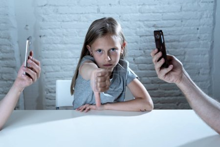 mother and father using mobile phones neglecting little sad ignored daughter bored and lonely feeling abandoned showing thumb down.  mobile cell smart phone addiction bad behavior concept