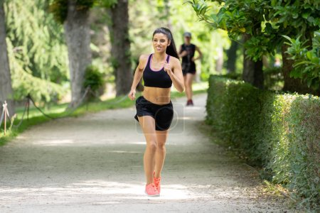 Photo for Young attractive and happy runner woman in Autumn sportswear running and training on jogging outdoors  in city park with trees and yellow leaves. fitness and healthy lifestyle concept - Royalty Free Image