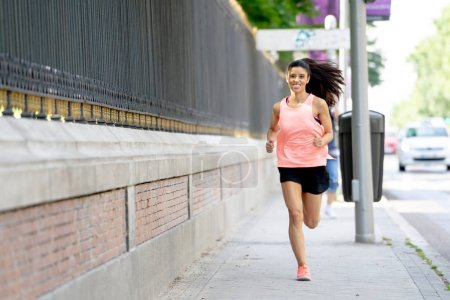 attractive young latin female runner jogging on the city street with traffic on the road in a  city environment