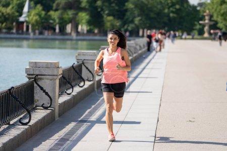 Photo pour Jeune coureuse séduisante et heureuse en automne vêtements de sport courir et s'entraîner au jogging en plein air dans le parc de la ville avec des arbres et des feuilles jaunes. concept de conditionnement physique et mode de vie sain - image libre de droit