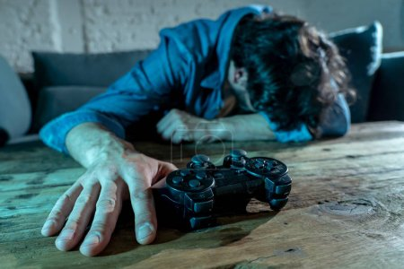 Photo for Addiction and dependency concept. close up on young man  with pad joystick playing video games Male addicted to console gaming concept. - Royalty Free Image